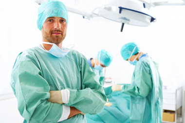 A portrait of a surgeon while an operation is being conducted in the background.