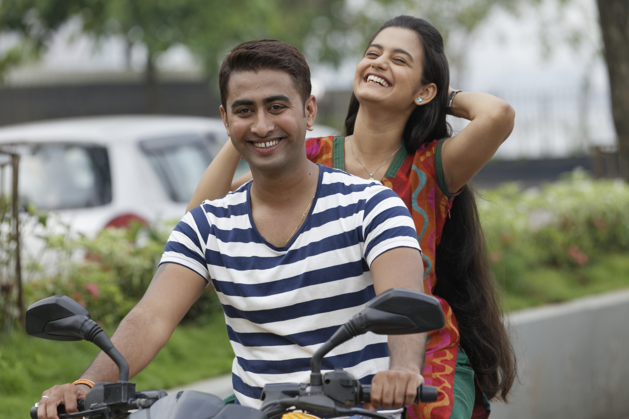 Indian young couple riding motorbike in India.
