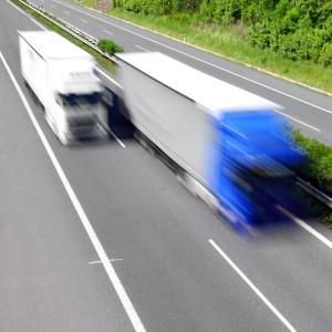 Motion blurred trucks on highway.