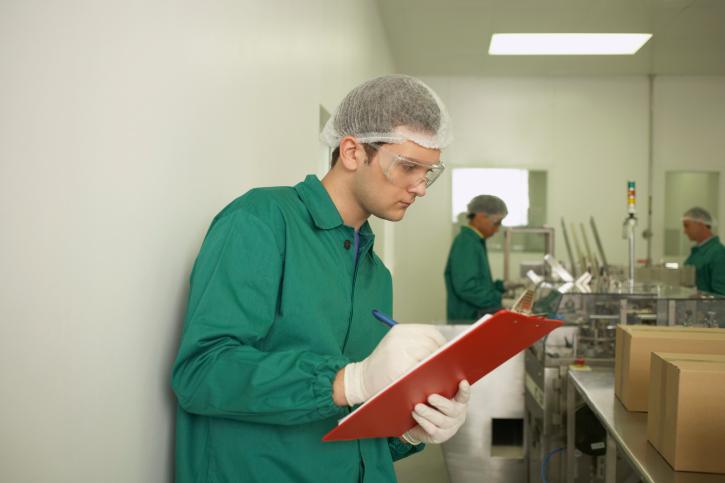 Lab technician writing on clipboard